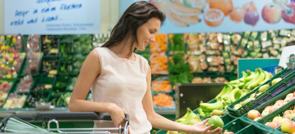 Donna che fa la spesa nel reparto frutta e verdura