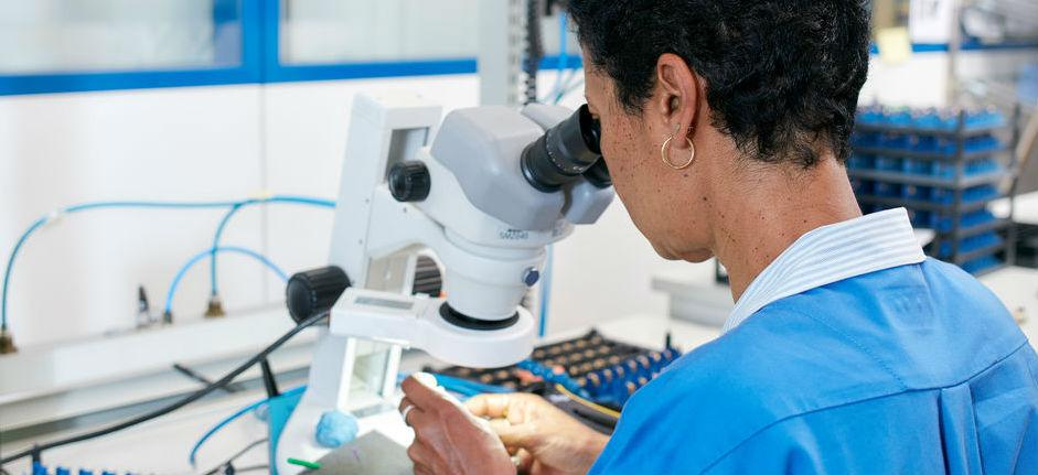 Woman examining samples under the microscope
