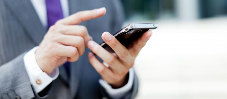 A businessman uses a smartphone to access various regulation-oriented services.