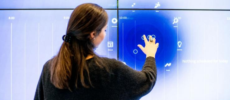 Woman at big touch screen.