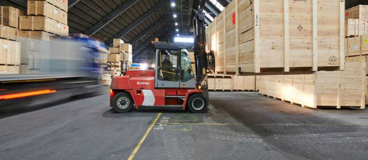 Forklift truck in warehouse lifts large wooden box