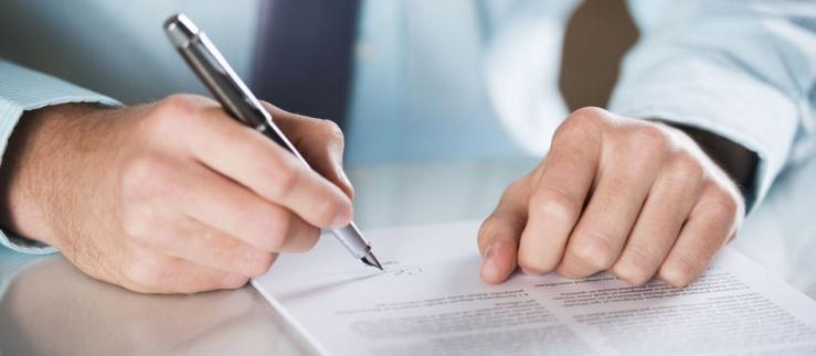 Close view of a man's hand, signing a contract
