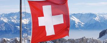 Swiss flag with mountains in the background