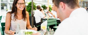 young man and woman eating lunch, outisde in a restaurant.