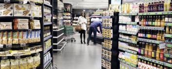 A food store with customers standing in front of a shelf.