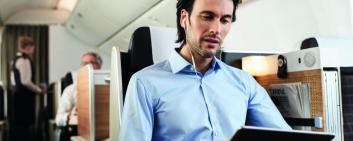 A man with headphones and a tablet is sitting in an airplane.